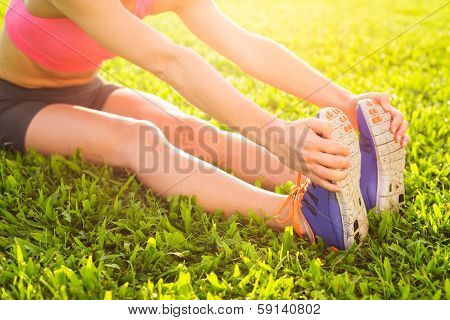 Attractive fit young woman stretching before exercise workout, sunrise early morning backlit, shallow depth of field, focus on shoes