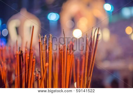 Red incense sticks burning in bokeh night