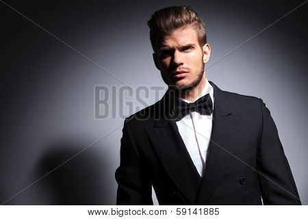 handsome man in tuxedo and bow tie in a dramatic pose on gray background