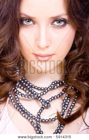 portrait of thoughtful young woman with professional make-up and beads