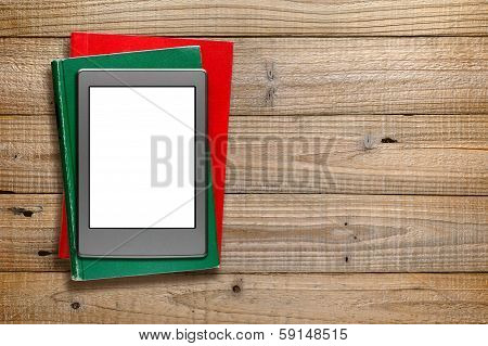 E-reader And Old Books On Wooden Background