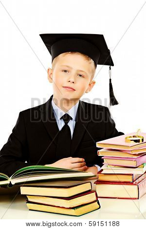 Serious schoolboy in academic hat sitting at the table with books. Isolated over white.