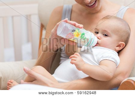 Closeup of a mother feeding baby with milk bottle at home
