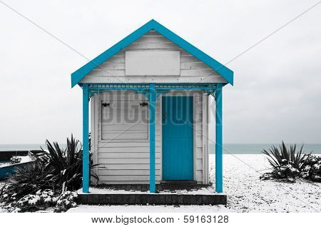 White and blue shed on a snow covered beach