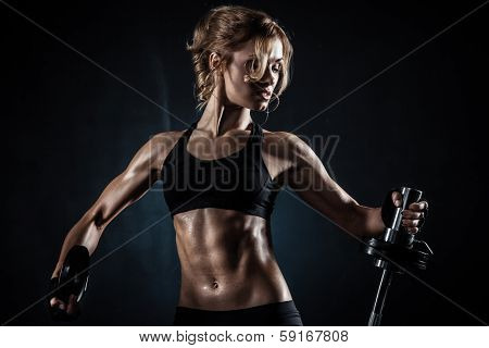 Brutal athletic woman pumping up muscules with barbell