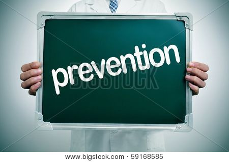 a doctor in white coat showing a chalkboard with the word prevention written in it