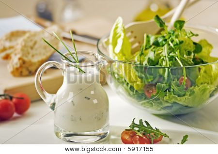 Bowl Of Greens And A Jug Of Salad Dressing