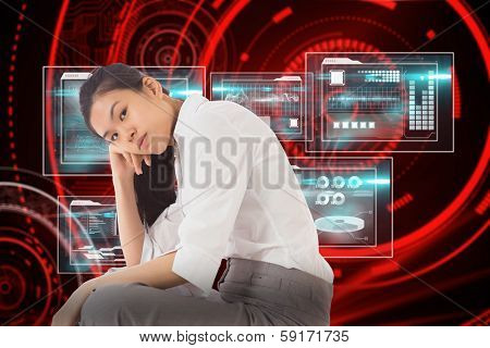 Businesswoman sitting cross legged leaning on hand against shiny red circles on black background