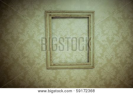 Empty vintage wooden picture frame hanging at an angle on old-fashioned beige wallpaper with an arabesque pattern with corner vignetting