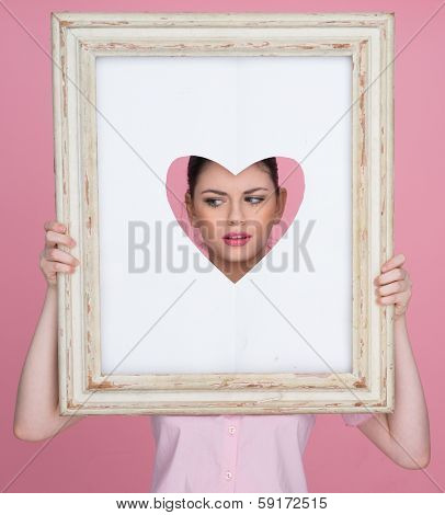 Beautiful young woman with her face framed by a heart as she looks through a cut out heart shape in an old vintage picture frame while posing for her sweetheart for Valentines Day