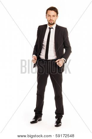Stylish successful young businessman standing looking confidently at the camera with an unbuttoned suit jacket, full length on white