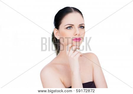 Beautiful woman standing daydreaming looking up into the air with a faraway expression and her hand to her chin, isolated on white
