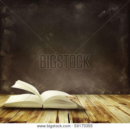 Open book on floor in front of blackboard