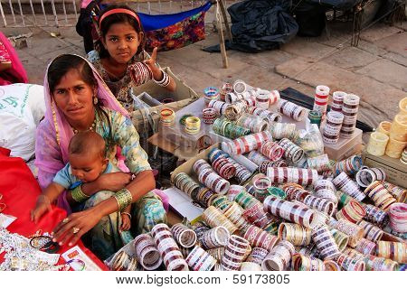 JODHPUR, INDIA - FEBRUARY 11: An unidentified woman with unidentified kids sells bangels at Sadar Ma