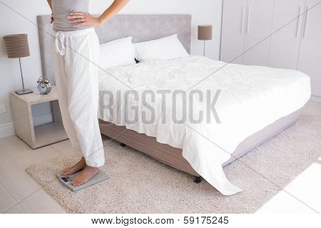 Side view low section of a fit young woman standing on scale in bedroom at home