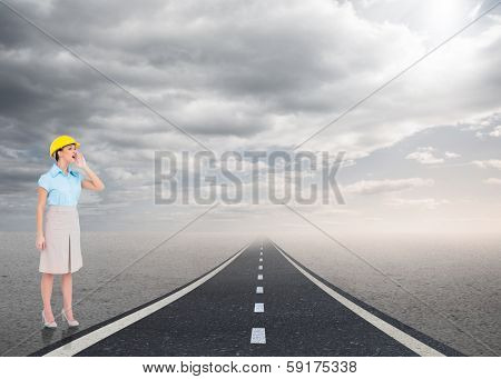 Attractive architect yelling against road leading out to the horizon