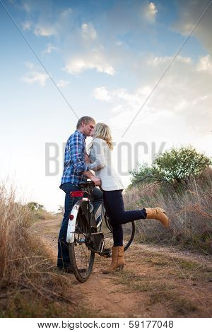 Young Adult Couple With Old Bicycle Kissing