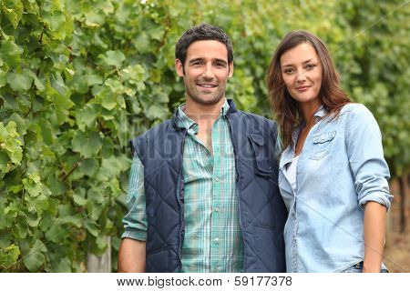Couple standing amidst vines