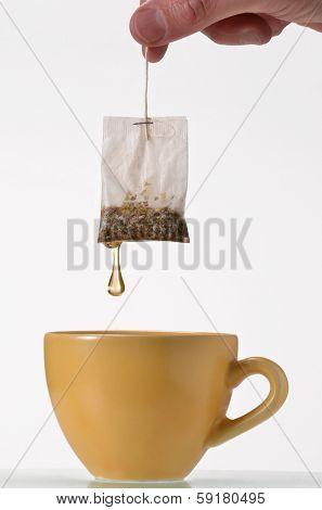 soaking a tea bag on a yellow cup,Tea bag on cup.Holding tea bag.
