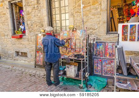 MONTREAL, CANADA, OCTOBER 12, 2013 - artist painting and selling his art in the street of Old Montreal