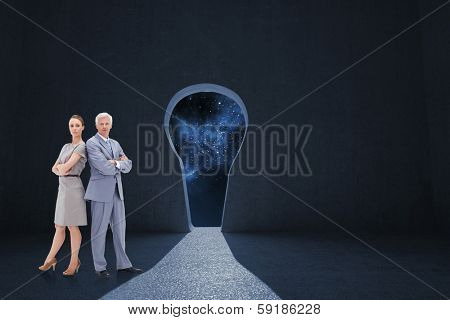Serious businessman standing back to back with a woman against keyhole door in dark room