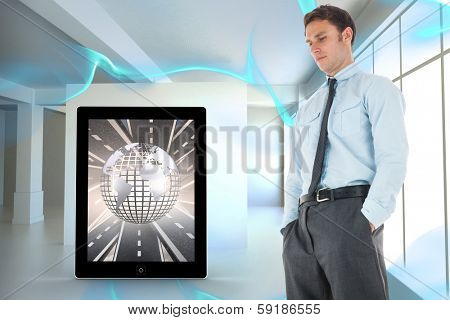 Serious businessman standing with hands in pockets against blue abstract design in room