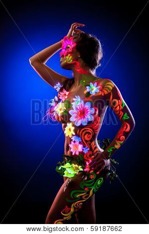 Sexy model posing with glowing flowers - uv light