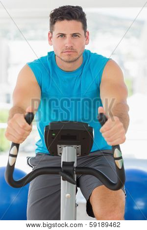 Portrait of a serious young man working out at class in gym