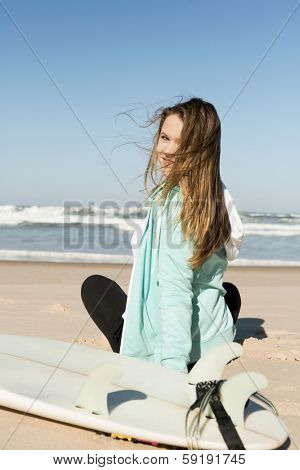 Tenage girl in the beach with her surfboard and loocking back