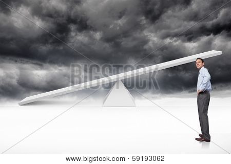 Smiling businessman with hand on hip against white scales in front of storm clouds
