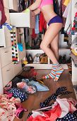 Getting dressed concept woman wearing underwear in walk in closet choosing clothes