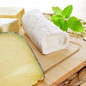 stock photo of brie cheese  - closeup of a wooden chopping board with an assortment of cheese - JPG
