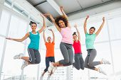 stock photo of slender  - Full length portrait of fitness class and instructor jumping in fitness studio - JPG