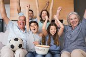 pic of extended family  - Portrait of happy extended family watching tv on sofa in the living room at home - JPG