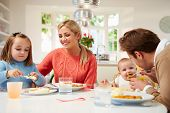 Family With Young Baby Eating Meal At Home