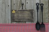 stock photo of wood craft  - Blank wood sign next to cast iron spoon and fork and red gingham  - JPG
