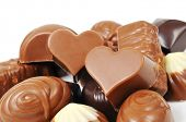 a pile of different chocolate bonbons, some of them heart-shaped, on a white background
