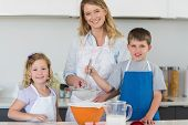 stock photo of flour sifter  - Portrait of mother with son and daughter baking cookies at counter top in kitchen - JPG
