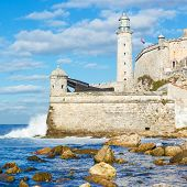 The lighthouse and fortress of El Morro in Havana with waves beaking against the wall