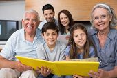 stock photo of extended family  - Portrait of an extended family looking at their album photo in the living room - JPG