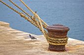 stock photo of bollard  - Rusty mooring bollard with ship ropes on Zadar docks - JPG