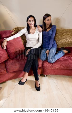 Mother and daughter sitting together on sofa