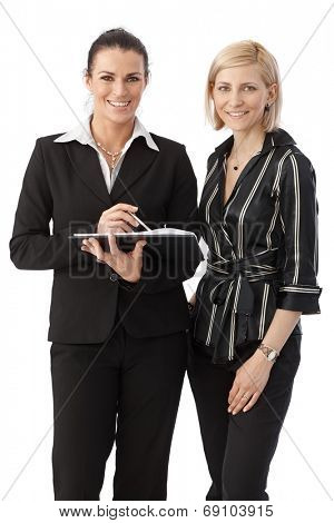 Group portrait of elegant happy caucasian, brunette and blonde office workers. Smiling, looking at camera, personal organizer in hand, white background.