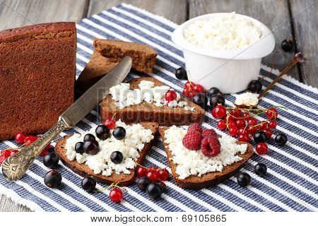 Bread with cottage cheese and berries on napkin close-up