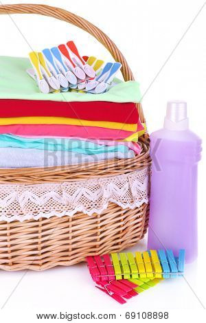 Bright clothes in laundry basket, pins and bottle with shampoo for washing, isolated on white