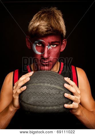 portrait of basketball player with turkish flag painted on his face