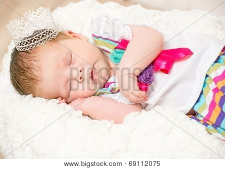 beautiful baby girl wearing a crown on a head sleeping