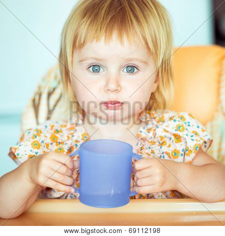 beautiful little girl sitting in a highchair and drinks