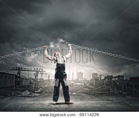 Strong man in uniform tearing metal chain with hands