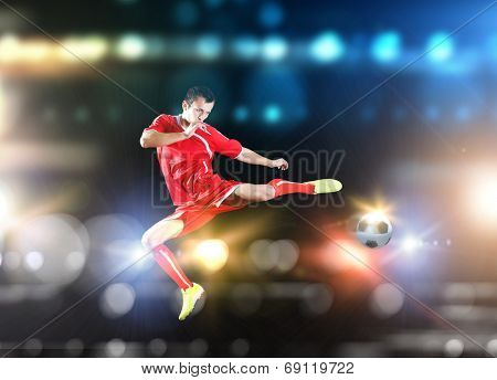 Young football player on stadium in jump taking ball
